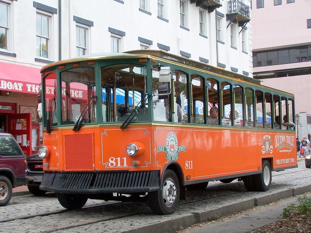 orange trolley with a few people in it