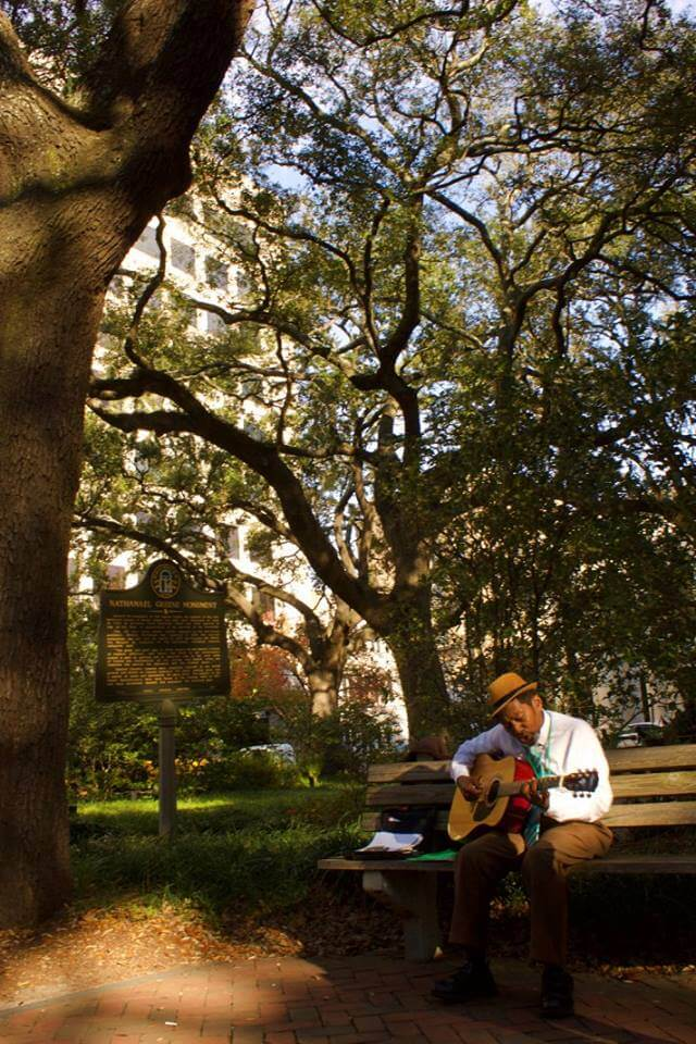 man playing guitar on a bench under a large oak tree