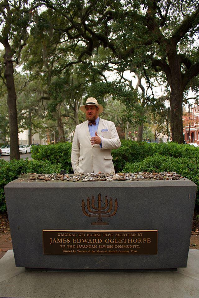 Tour guide talking in Savannah behind Jewish memorial