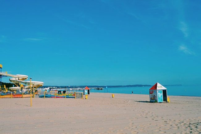blue sky above sandy beach and sea with beach hut