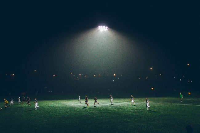 people playing soccer on green field beneath light at night