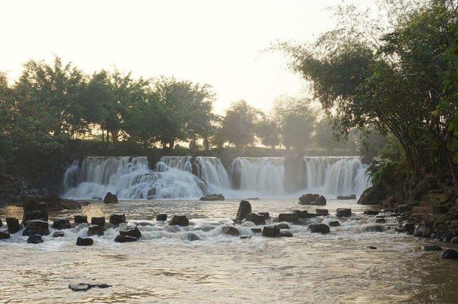 set of waterfalls in background below hazy sky