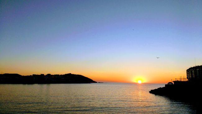 sun setting behind the ocean and against a blue sky