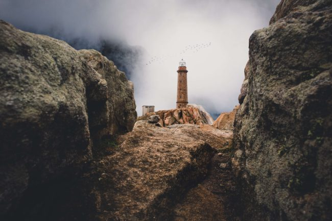 foggy view out over a tower between rocks