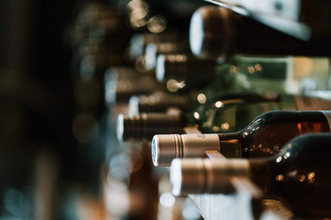 top of wine bottles in rack