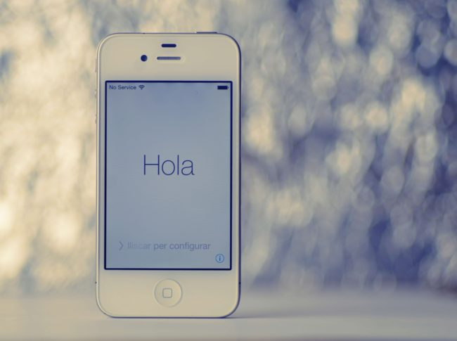 hola on iPhone held up again white and gray background