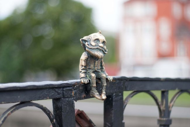 small gnome sitting on fence in Wroclaw Poland