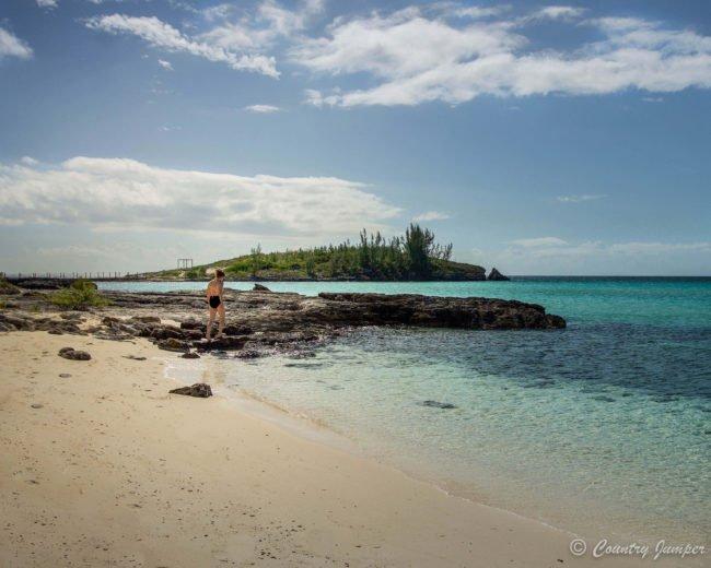 woman in bikini walking on the beach in the Bahamas