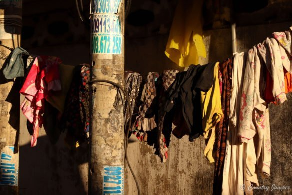 clothes hanging on a line against a concrete wall