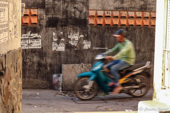 blue motorbike in motion with man in green shirt riding