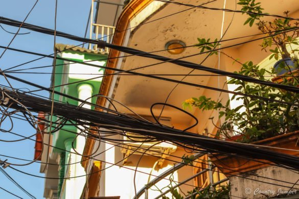 Electric wires together against a backdrop of rooves