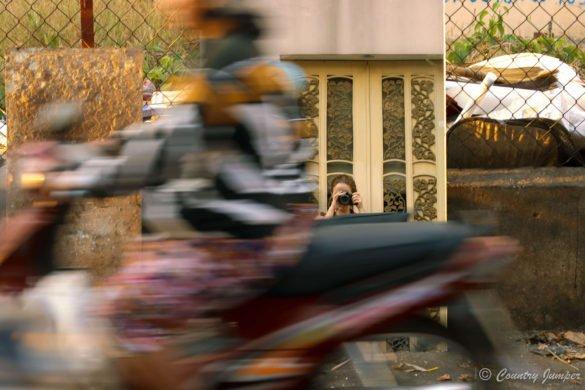 selfie of photographer in mirror behind motorbike going past