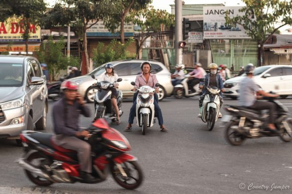 an intersection with many motorbikes and a few cars trying to get through