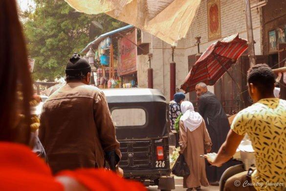 man in brown shirt walks down crowded street