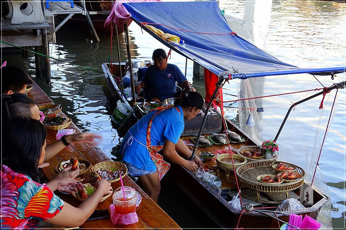 women preparing food on a boat at a floating market in thailand