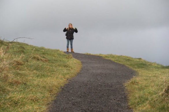 Girl in black jacket standing onto of a hill