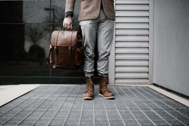 Lower half of man holding leather backpack in hand