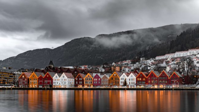 a row of houses in Norway reflected on the water