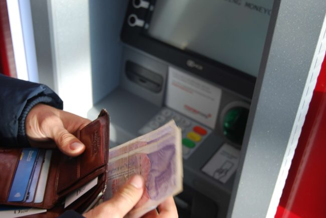 man holding one and wallet next to atm