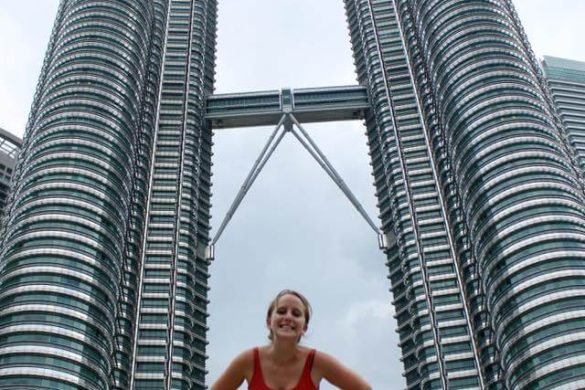 girl in red strapless dress with hands on hips smiling between petronas towers in Kuala Lumpur Malaysia