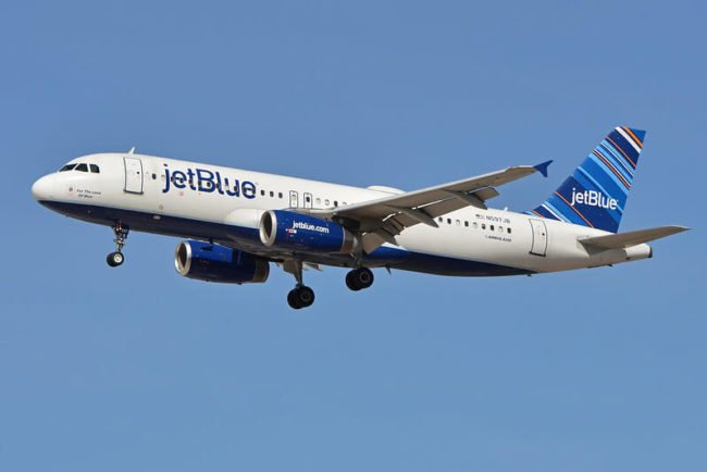 JetBlue airplane flying in blue sky