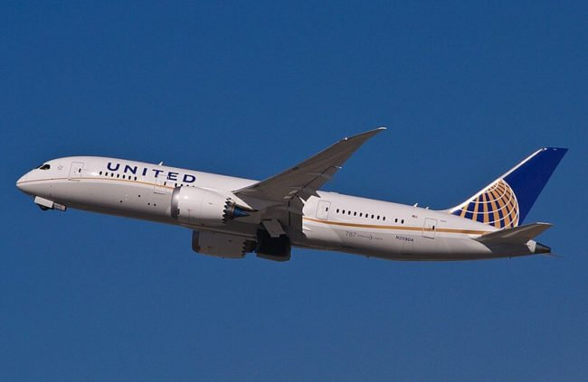 white united airlines plane taking off to the left against a blue sky