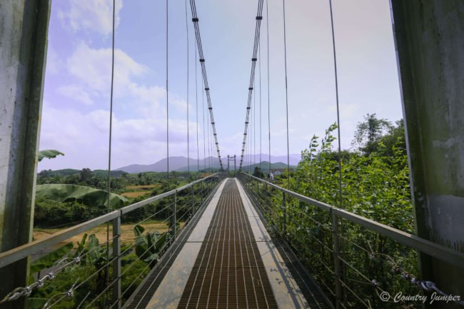 brown straight suspension bridge running into horizon dividing blue cloudy sky with green below