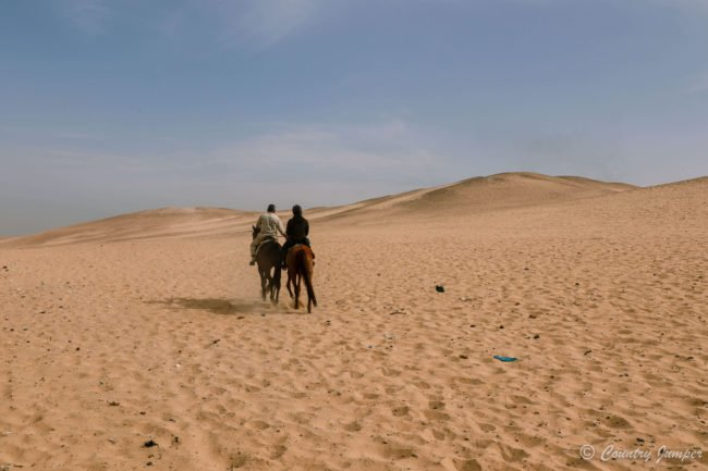 two people riding horses in open desert beneath blue sky in Cairo egypt