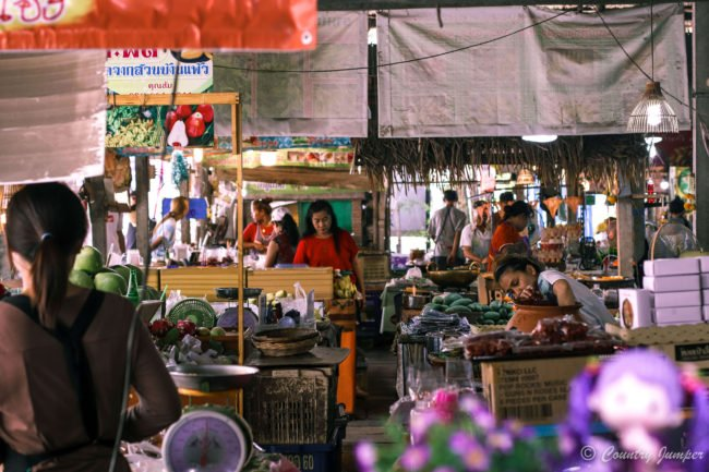 purple flowers in foreground, women in market in middle, layers of market stalls