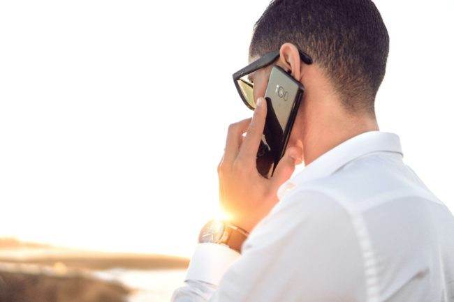 man in white shirt with glasses talking on cell phone