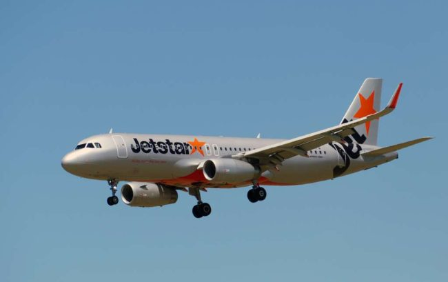 silver jetstar plane flying against blue sky