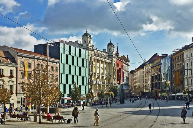 building around left side, tram track through center, some people walking in the street, building on the right
