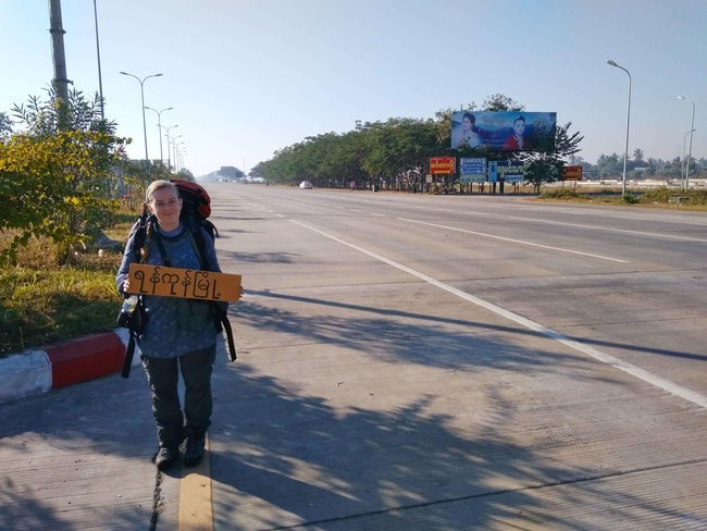 woman standing on side of road holding sign for hitchhiking