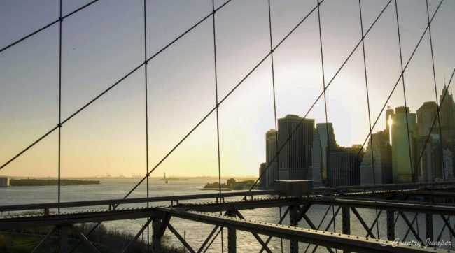 New York city skyline through wires of Brooklyn bridge over river
