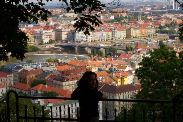 woman looking over shoulder with view of Prague in the background