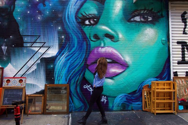 large blue mural of face of woman with another woman walking past