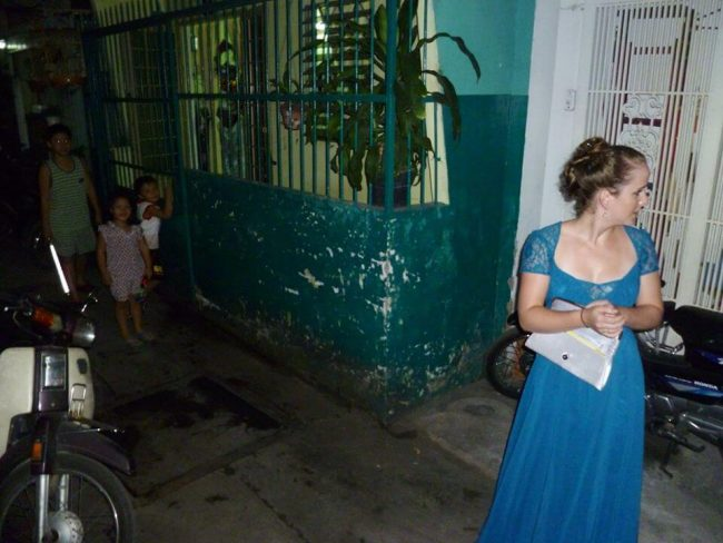 white girl standing in Vietnamese alleyway in ballgown