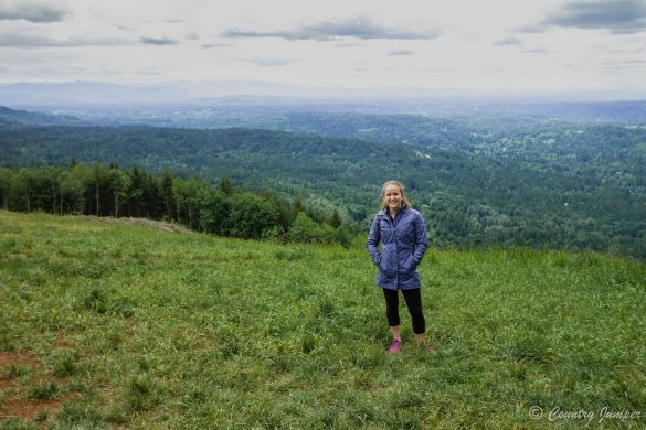 woman in blue jacket standing at top of poo poo point mountain