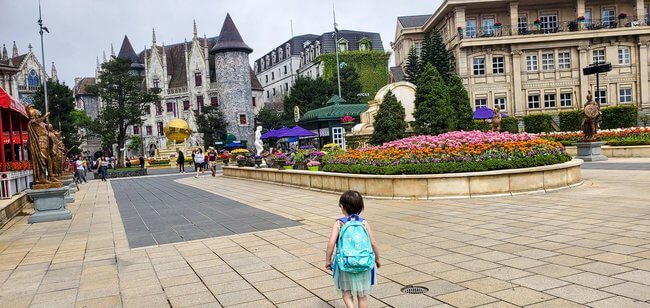 child with blue backpack in pedestrian area