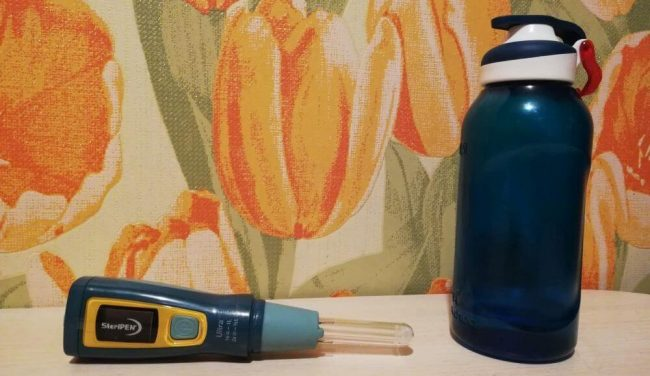 stripes and water bottle on shelf in front of floral wallpaper