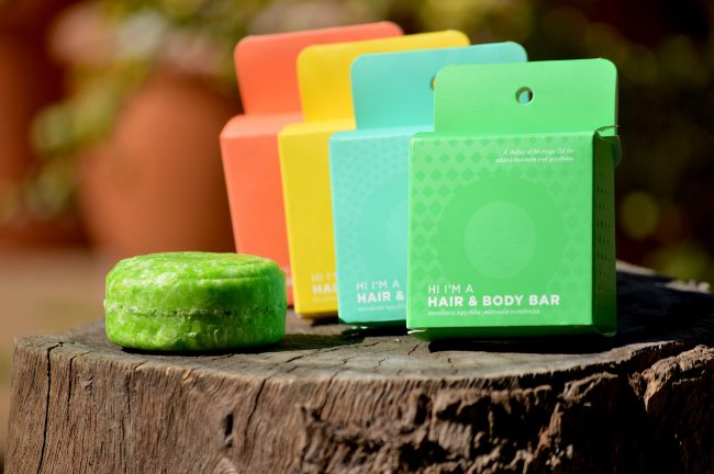 orange, yellow, blue, and green boxes for shampoo bars with green bar in front