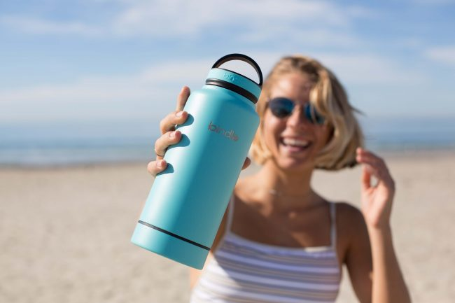 woman smiling on beach holding blue reusable water bottle