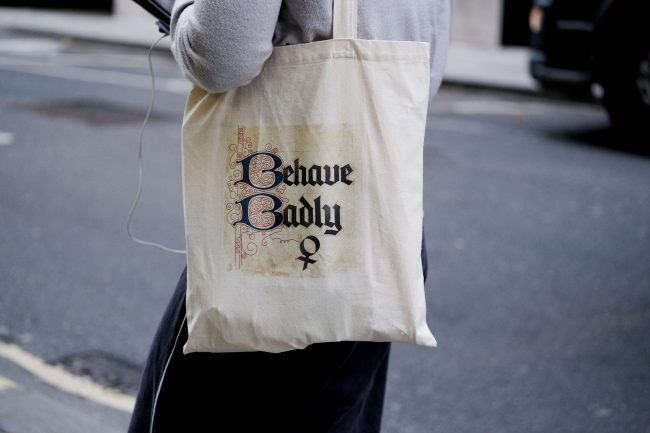 white tote bag with behave badly on the outside