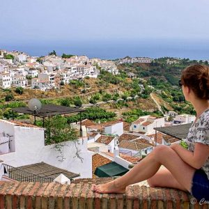 woman in white shirt sitting along brick wall looking out over white houses and ocean in the background