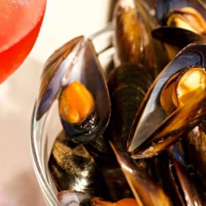 mussels in bowl net to glass of red drink